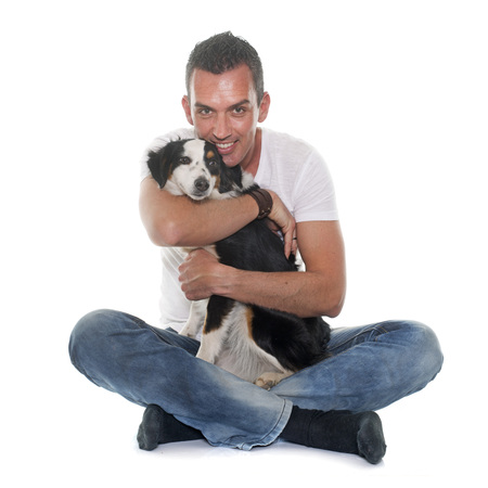 miniature collie: man and miniature australian shepherd in front of white background