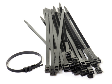 electric material: black cable ties in front of white background Stock Photo