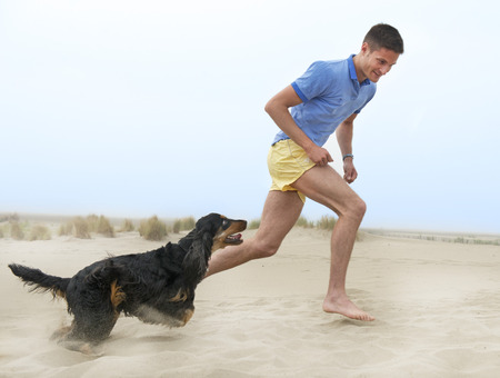 man dog: man playing with his dog on the beach