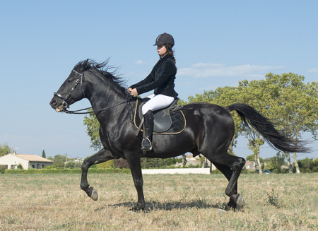 complicity: young girl riding a black stallion in a field Stock Photo