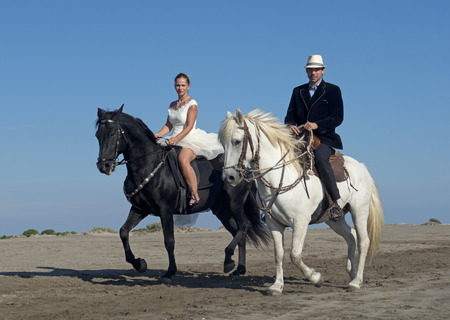 riding: marrieds and horses on a beach in the south of France