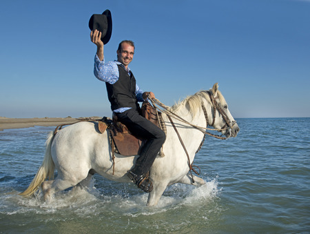 herdsman: herdsman and Camargue walking in the sea