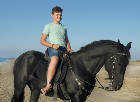 young boy and black stallion on the beach Stock Photo