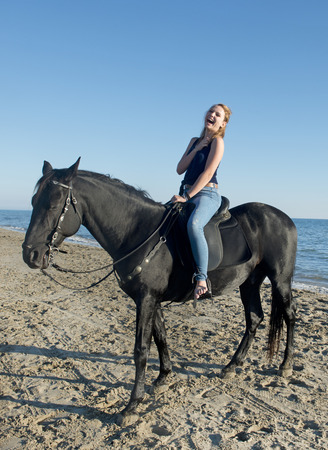 horse laugh: laughing woman and black horse on the beach