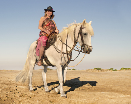 camargue: horse woman and her stallion riding on the beach Stock Photo