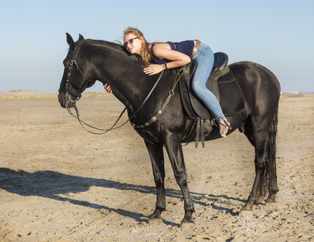 horse laugh: riding girl with her black  on the beach