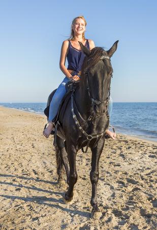 caballo de mar: chica de montar con su semental negro de risa en la playa