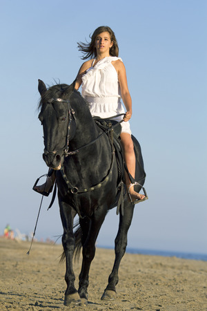 horse woman and her stallion riding on the beach