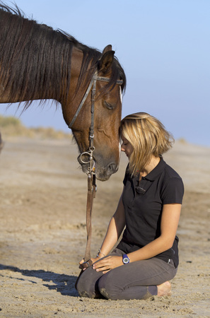 resting: horsewoman and her horse on the beach
