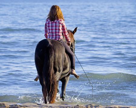 caballo de mar: mujer del caballo y su semental que monta en el mar Foto de archivo