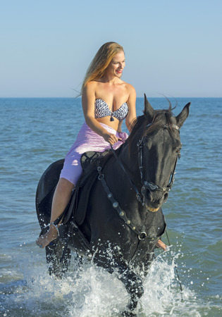 horse woman and her stallion in the sea Stock Photo