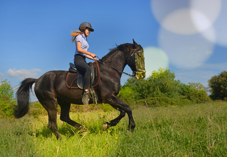 complicity: young riding girl and her black stallion in nature