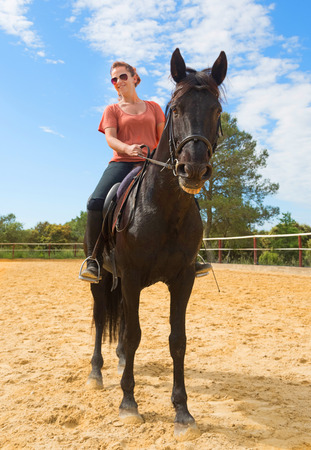 complicity: smiling riding girl and her black stallion in a training
