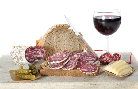 saucisson, bread and butter in front of white background