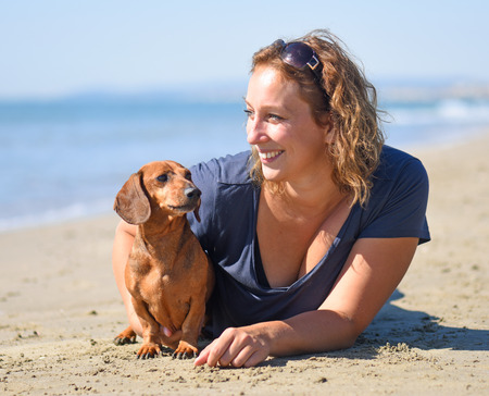 complicity: dog and woman on the beach in september Stock Photo