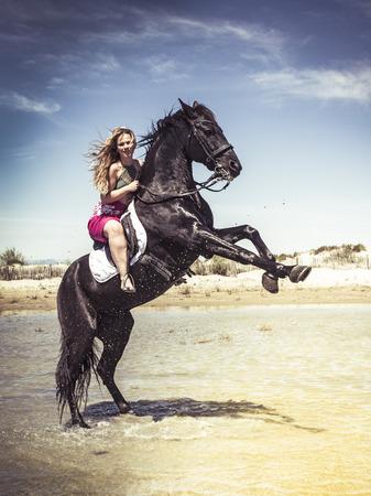 woman riding her black stallion on the beach