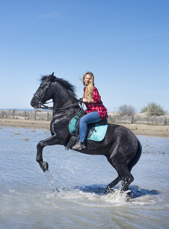 woman riding with her stallion on the beach