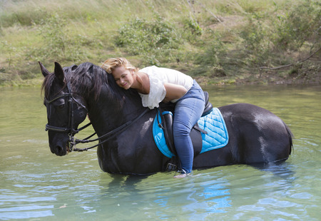woman rider and her black horse are walking in river