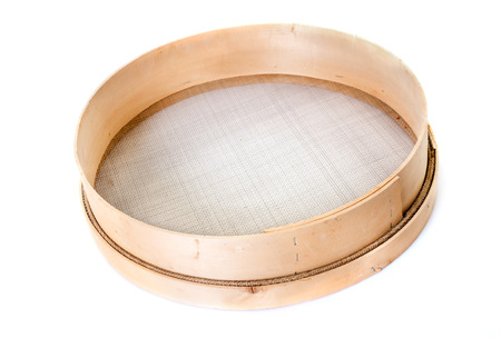 wooden sieve in front of white background