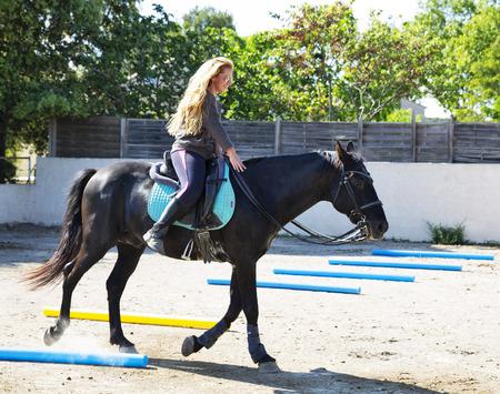 ragazza a cavallo sta addestrando il suo cavallo nero