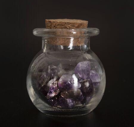 amethyst in flask in front of black background Banco de Imagens