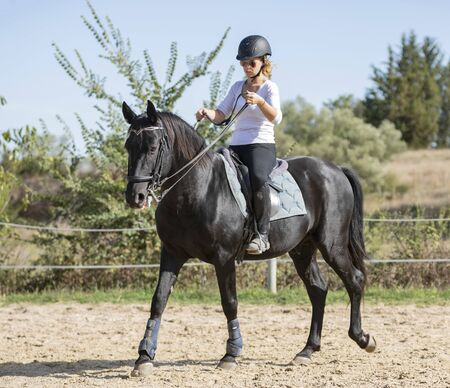 riding girl are training her black horse