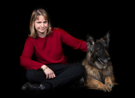 german shepherd and woman in front of black background
