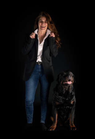 purebred rottweiler and woman in front of black background