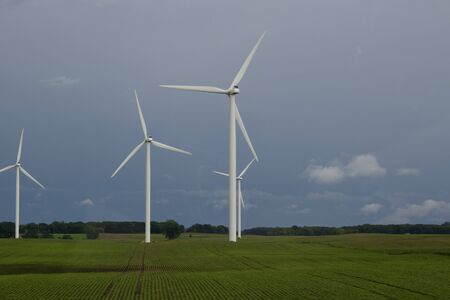 Giant wind turbines on an agricultural field with blue sky