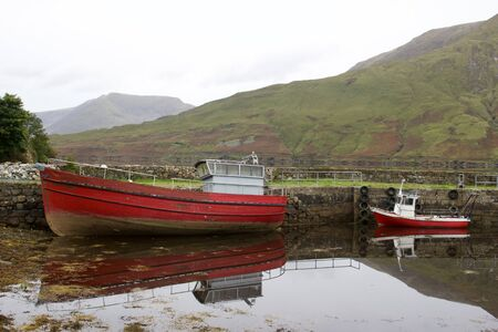 View of two small red boats along the banks of a lake in the Connemara region of western Ireland 版權商用圖片 - 130275542