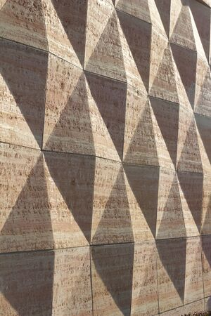 Exterior concrete wall texture with geometric shapes that are enhanced by late day sun shadows (angle view)