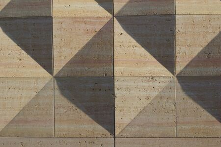 Exterior concrete wall texture with geometric shapes that are enhanced by late day sun shadows Stock fotó