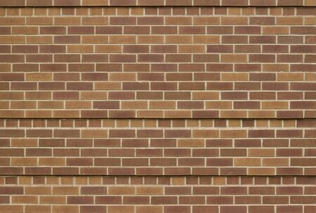 Brown brick wall texture background with unique accent rows of protruding bricks