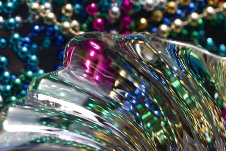 Macro abstract art texture of beautiful lead crystal glass with curved rippling surface and multi color metallic beads, reflecting brilliant light and color Stock Photo
