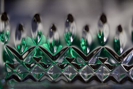Macro abstract view of a beautiful modern lead crystal glass surface with diamond cut accents reflecting green color