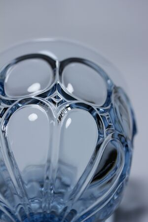 Macro abstract view of a beautiful vintage blue crystal glass goblet with white background
