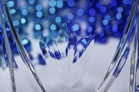 Macro view of a beautiful modern lead crystal glass surface with hand cut facets reflecting blue bokeh light 写真素材
