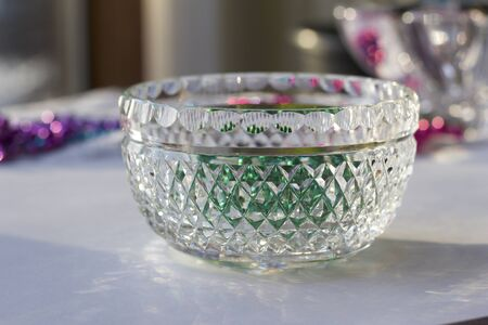 Macro view of a beautiful lead crystal glass bowl with hand cut diamond facets reflecting bright light