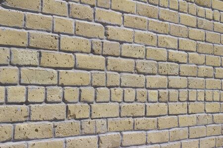 Antique shabby chic yellow beige color brick wall texture (angle view)
