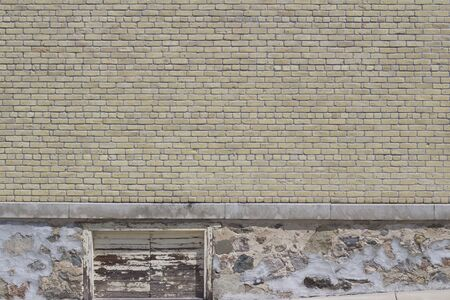 Antique shabby chic beige color brick wall texture with deteriorating white stone foundation and boarded up window Stok Fotoğraf