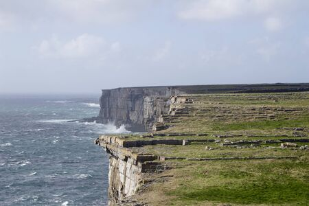 Landscape view of the rocky cliffs of Irelands west coast of Inis Mor, with blue sky and green rocky terrain Stockfoto