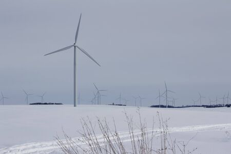 Giant wind generating turbines grace a quiet and peaceful rural snowy landscape 免版税图像 - 134211243