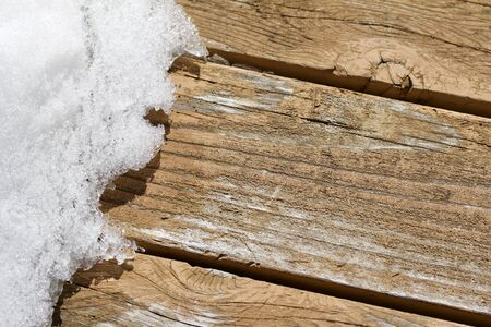 Macro view of melting snow and ice on a cedar deck floor