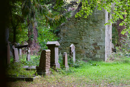Idyllic landscape view of a tiny 16th century cemetery in Europe in a quiet woodland setting