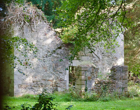 Ruins of an old 16th century stone building in a woodland setting in Europe