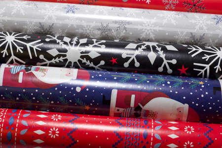 Close up texture view of rolls of generic Christmas holiday wrapping paper assortment, in rolls stacked side by side