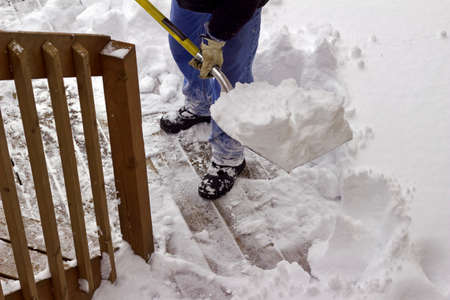 Close up view of an unseen person who is shoveling snow off a wooden deck surface