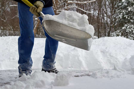 Close up view of an unidentifiable person shoveling heavy snow off a wooden deck surface