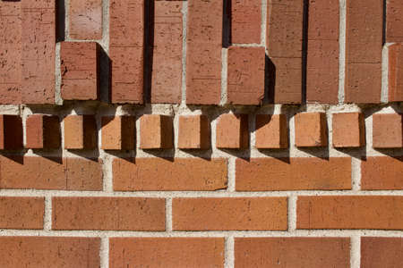 Vintage brown clay brick wall background with protruding bricks in varying geometric shape textures