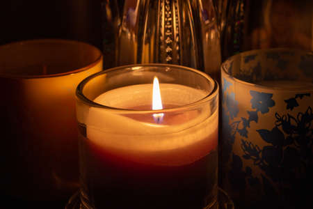Close up view of a single candle illuminating darken glass objects nearby